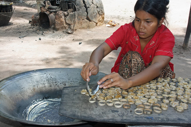 Villageoise confectionnant des bonbons au sucre de palme. Photographie par Matthew Klein (CC)