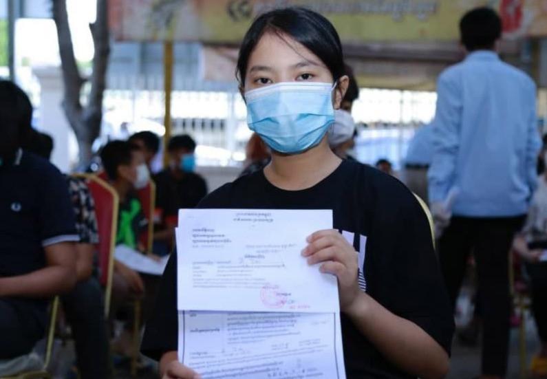 Adolescente cambodgienne montrant son certificat de vaccination (AKP)