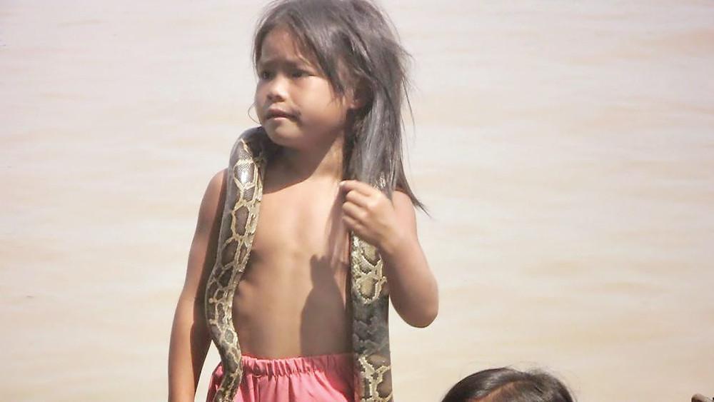 Jeune enfant Cambodgienne proposant une photo avec un python, aux touristes sur le Tonle Sap