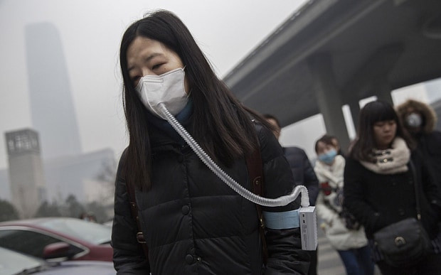 A Chinese woman wears a mask connected to a filter in Beijing, China