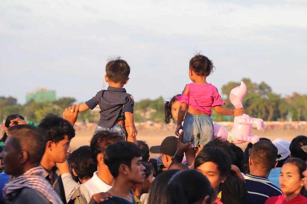 Des enfants hissés sur les épaules de leurs parents, aux premières loges pour la course de pirogues