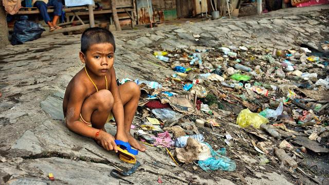 Enfant jouant prés d'un étang – dépotoir créé par les eaux usées et l'accumulation des ordures ménagères
