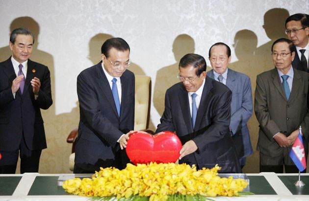 Le Premier ministre chinois Li Keqiang, à gauche, signe avec son homologue cambodgien Hun Sen, au centre, le symbole du Voyage Cœur Chine-Cambodge lors d'une cérémonie de signature au Palais de la Paix à Phnom Penh, au Cambodge, le 11 janvier 2018. La Chine a signé jeudi près de 20 accords valant plusieurs milliards de dollars pour développer les infrastructures, l'agriculture et les soins de santé du pays de l'Asie du Sud-Est.