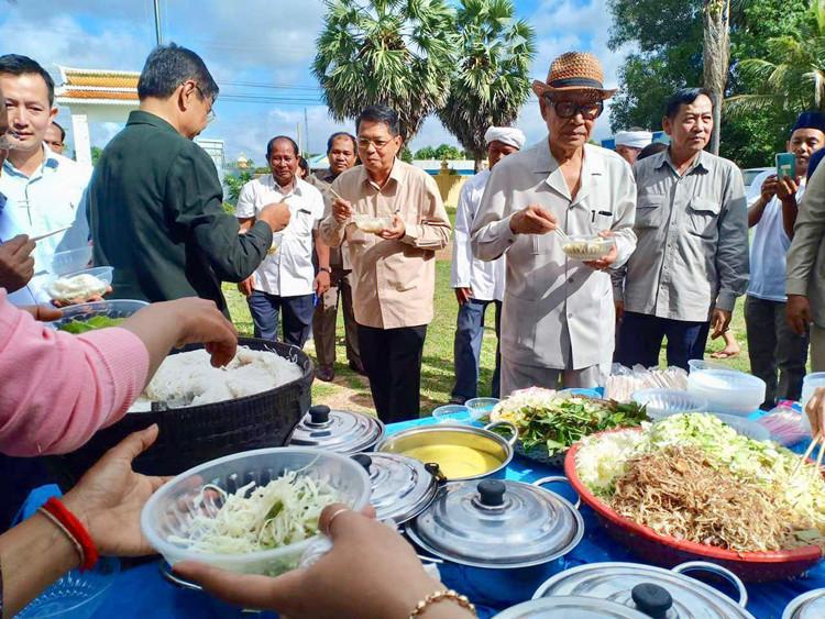 Samdech Chaufea Veang Kong Sam Ol mange du Num Banchok avec des habitants des districts de Kampong Tralach et Samaki Meanchey