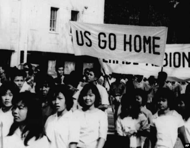 1964 : des écolières  portent des banderoles  «US Go Home» et «Perfidious Albion» à Phnom Penh