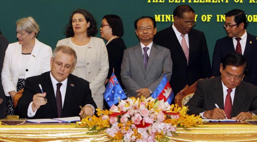 Le ministre australien de l'Immigration, Scott Morrison, à l'avant gauche, signe un document avec le ministre cambodgien de l'Intérieur, Sar Kheng, à l'avant droite, lors de la cérémonie de signature d'un accord controversé sur la réinstallation des réfugiés au sein du ministère de l'Intérieur à Phnom Penh, au Cambodge, le vendredi 26 septembre , 2014.