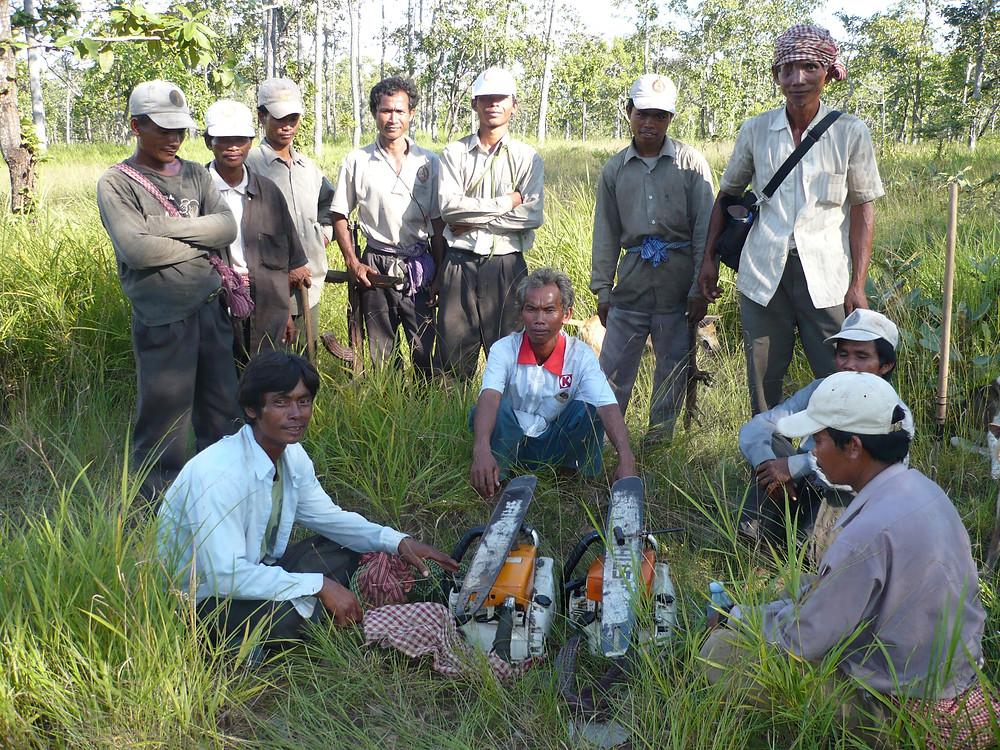 Une patrouille forestière de la communauté autochtone Kuy pose avec deux tronçonneuses illégales qu'elle a capturées lorsque la patrouille a surpris des bûcherons illégaux au travail et provoqué leur fuite en laissant derrière eux leurs tronçonneuses