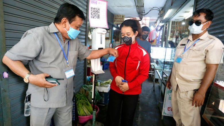Un agent de sécurité vérifie la carte de vaccination d'un vendeur du marché de Psar Chas avant son entrée dans le district de Daun Penh de la capitale. Heng Chivoan
