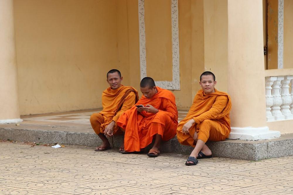 Des moines bouddhistes assis devant le Palais Royal