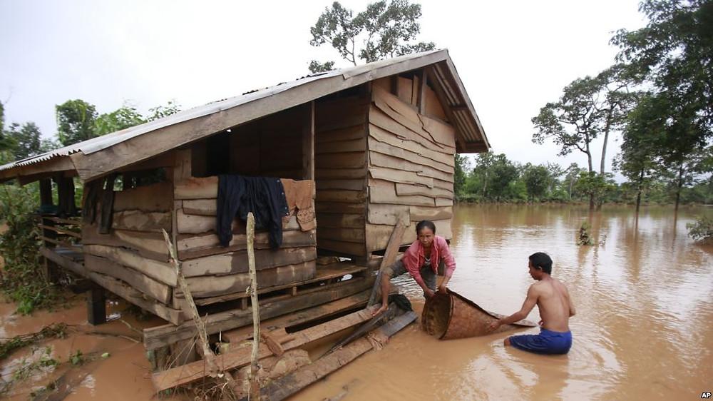 Kongvilay Inthavong et son épouse Thongla nettoient leur maison alors que les eaux commencent à se retirer dans le district de Sanamxay, province d'Attapeu, au Laos, le jeudi 26 juillet 2018. Les autorités et le constructeur enquêtent sur l'effondrement d'un barrage au moins deux douzaines de personnes et laissant plus de cent personnes portées disparues. (AP Photo / Hau Dinh)