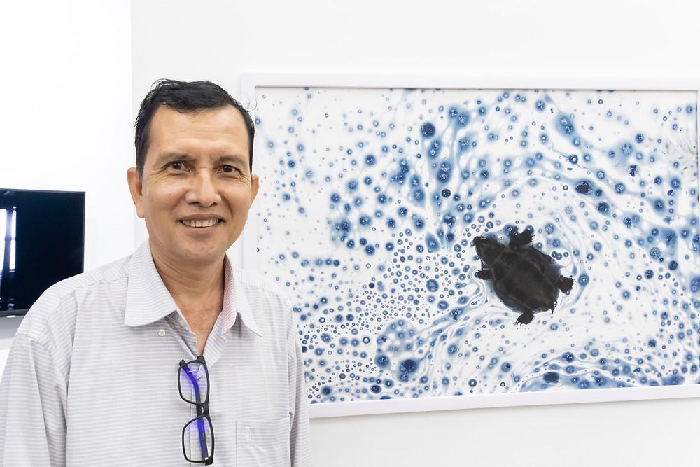 Mak Remissa, «parrain» d'une nouvelle génération d'artistes, pose devant l'une de ses œuvres