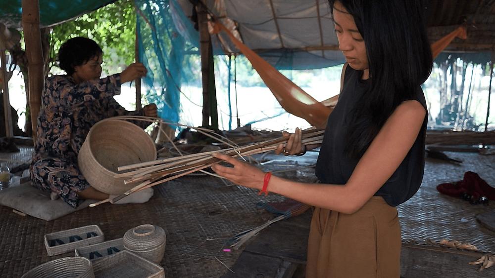 Ka-Lai montre du rotin, la plante utilisée pour créer leurs produits