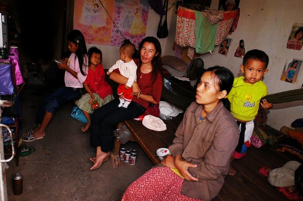 Orn Sreymom, 22 ans (devant) et Orn Cheang, 33 ans (tenant un bébé) sont des soeurs. Les deux sont des travailleurs du vêtement. Il y a deux ans, ils ont quitté leur ville natale de Kampong Cham pour chercher un emploi à Phnom Penh. Ils vivent avec 8 autres membres de la famille, âgés de 5 mois à 55 ans, dans une chambre louée de deux lits et une toilette de 4 mètres carrés. Le mari de Sreymom et sa sœur cadette travaillent également dans des usines de confection. Chacun gagne environ 50 à 70 dollars par mois, y compris les heures supplémentaires. Leur mère s'occupe des petits-enfants pendant les quarts de travail