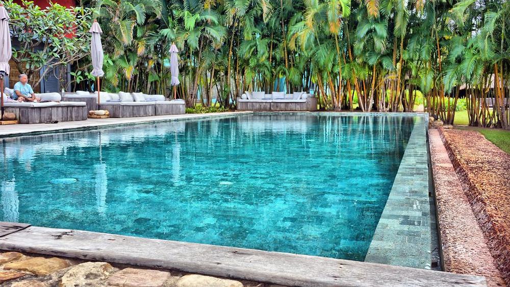 Une piscine est construite à l'orée du jardin, où dorment de grands arbres