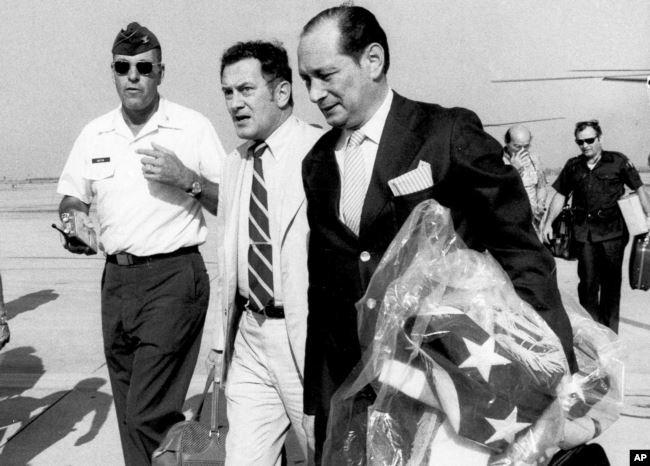 Dans cette photo du 12 avril 1975, l'ambassadeur des États-Unis au Cambodge, John Gunther Dean, porte le drapeau américain de l'ambassade des États-Unis au Cambodge alors qu'il arrive à la base aérienne de Utapao en Thaïlande après l'évacuation de Phnom Penh.