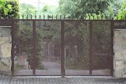 Puerta batiente de dos hojas con chapa troquelada y puntas de lanza