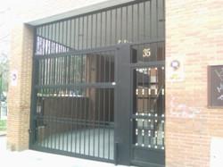 Puerta basculante con tubos verticales de 20x20 y peatonal entrada a portal insertada