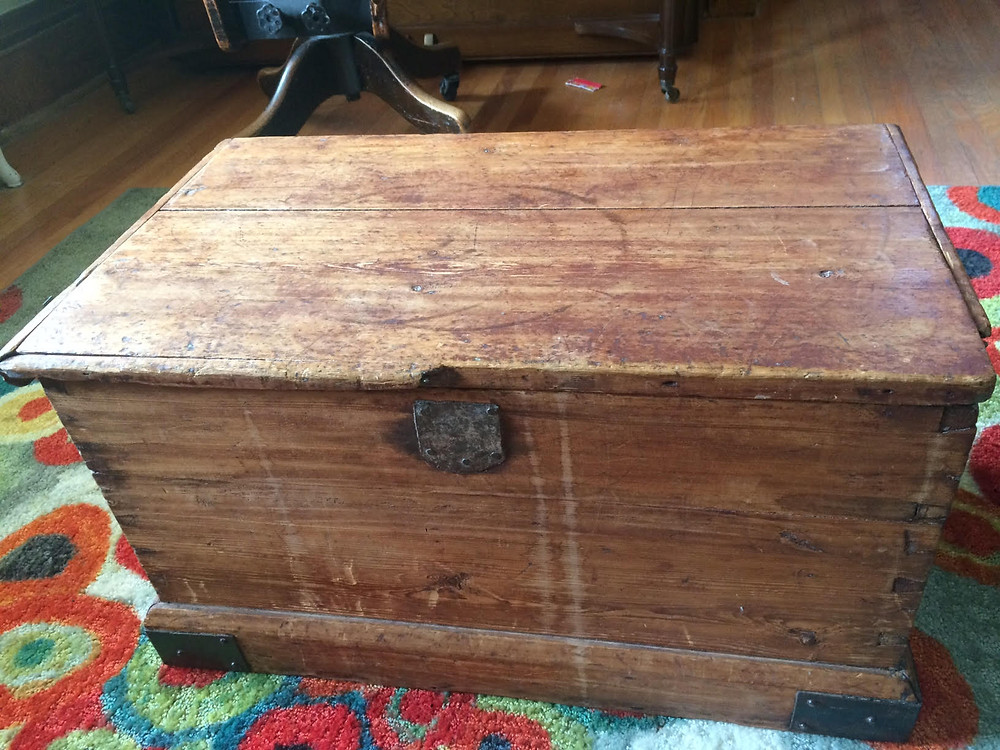 Image of an antique trunk with a broken clasp and ring marks on top.