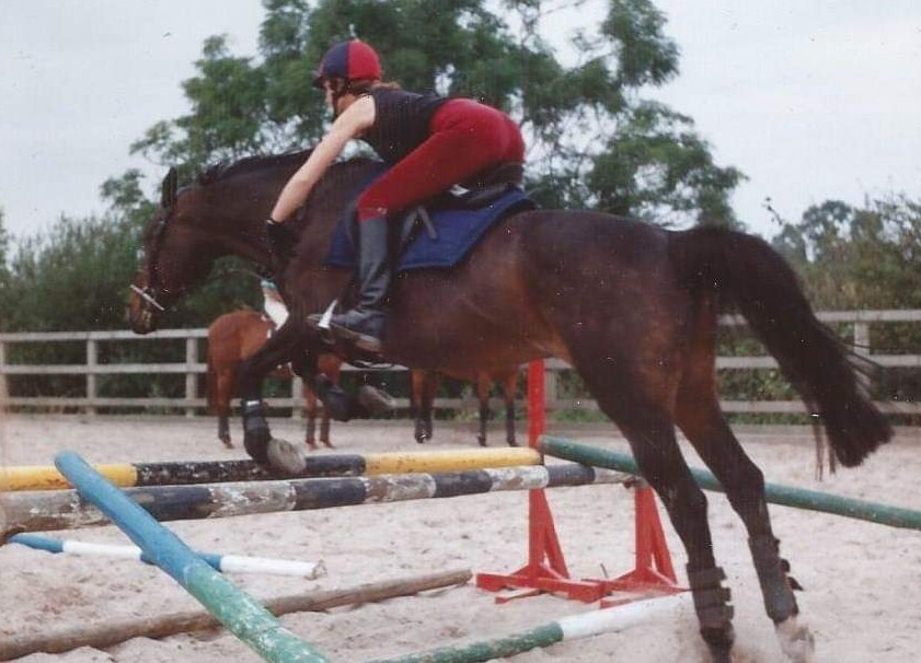 Ros on first horse jumping a small spread. Horse has dropped one front leg a bit too low