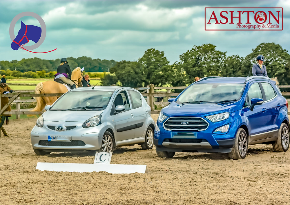 2 cars parked side by side st the end of a dressage arena. one for the judge, the other for the writer