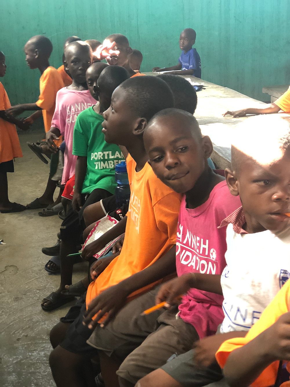 Children in The Sanneh Foundation shirts wait for their English lesson to continue.