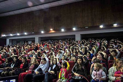 a Hall full of people with their hands on their heads, taking their Self Realisation