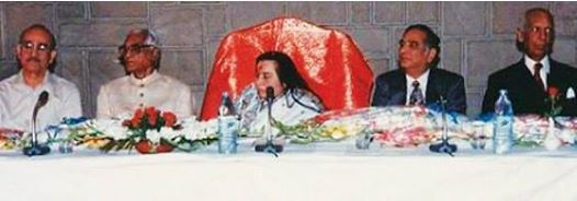 Photo of Shri Mataji sitting at a long table amongst dignitries