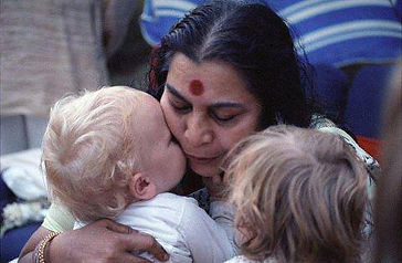 Shr Mataji, getting kissed by little baby boy and another child standing next to her as if waiting for her turn. A beautiful picture