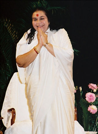 A Photo of Shri Mataji in a white sari standing with hands in a Namaste position