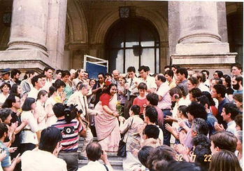 Photo of Shri Mataji outside on the step of a Hall, surrounded by lots of people including photographers and camermen,wanting to see her and holding their hands out to receive Her vibrations.