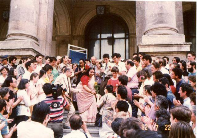 Shri Mataji (on the steps in front of the hall being greeted and welcomed by a crowd of people, including reporters etc.
