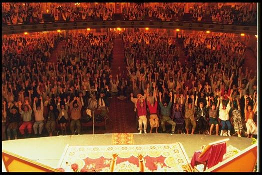 A photo taken at Royal Albert Hall, UK, of thousands of people with their hands out stretched receiving the Self Realisation from Shri Mataji