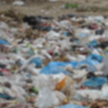 Land covered with mainly white and blue plastic bags and rubbish