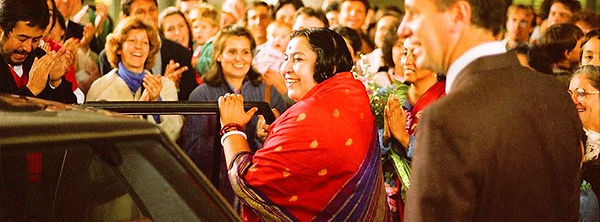 Photo of Shri Mataji surrounded by Sahaja Yogis/ people, all full of joy on their faces. The Mother is about to get into her car...like a departure...