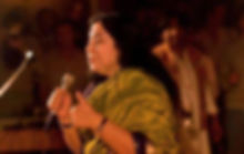 Shri Mataji with a mike in a her hand standing on a stage, talking to people