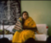Photo of H H Shri Mataji Nirmala Devi, sitting and teaching Sahaja Yoga.  They is a huge black board behind her withthe subtle system drawn on and labelled