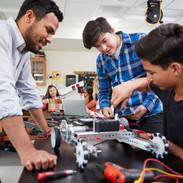 Teacher With Male Pupils Building Roboti