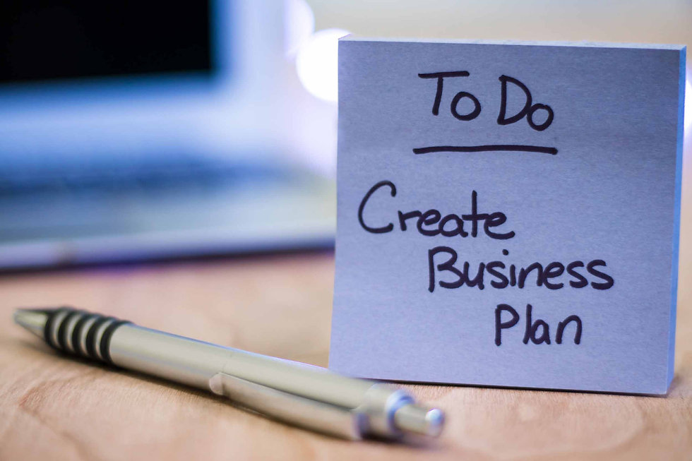 To do list with create business plan written on sticky note with pen