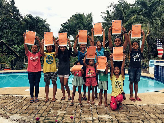 Filipino kids proud to show the Eco Warrior Mermaid code of conduct they signed