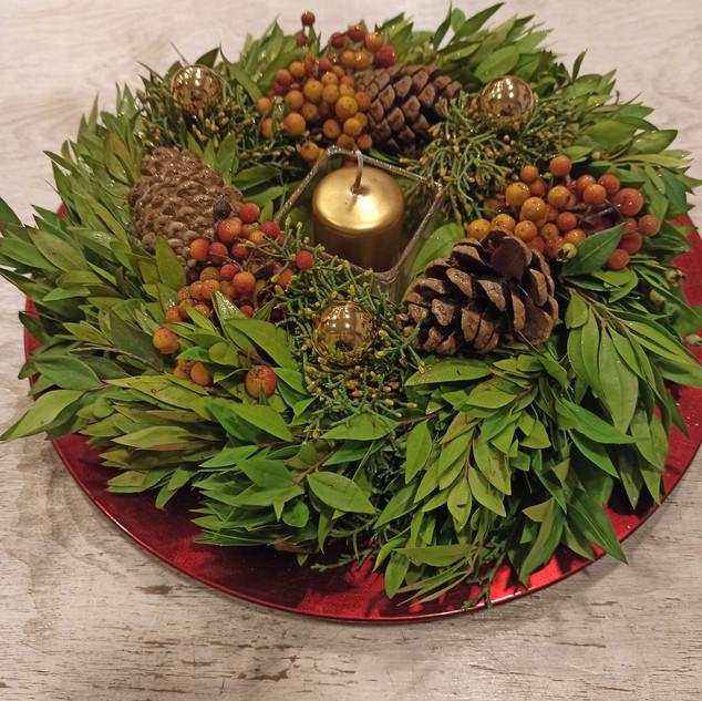 Centro-Tavola su piatto rosso con frutta, pigne e candela
