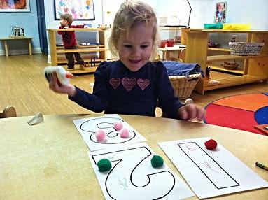 Montessori of Camden student with glue and classwork