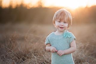 toddler wearing blue dress in a field