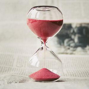 Grains de sable rouge qui s'écoule à l'intérieur d'un sablier en verre. Concept du temps.