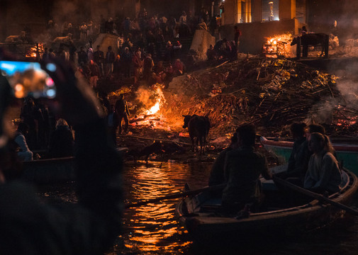 A tourist grabbing an iPhone snapshot of the funeral ghats in Varanasi, India.