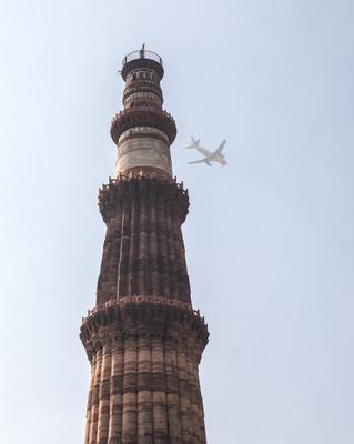 A jet flies high above the Qutub Minar in New Delhi, India.