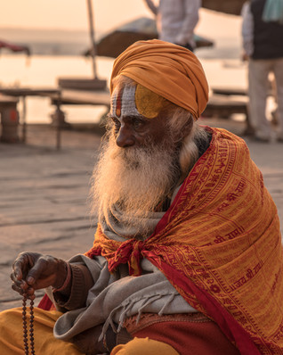 A man dressed as a sadhu poses for a tourist, who likely paid him a few hundred rupees for the photo op.