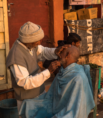 A barber shaves a client just after sunrise in Varanasi, India.