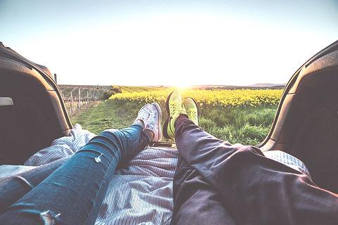 couple lying down in grass between fields