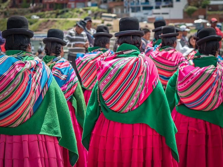 Cholitas, wearing pink pleated skirts, g