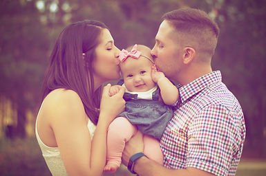 parents kissing their child